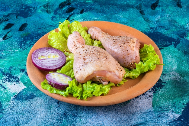 Cebolla hojas de lechuga y muslo de pollo en una placa de arcilla