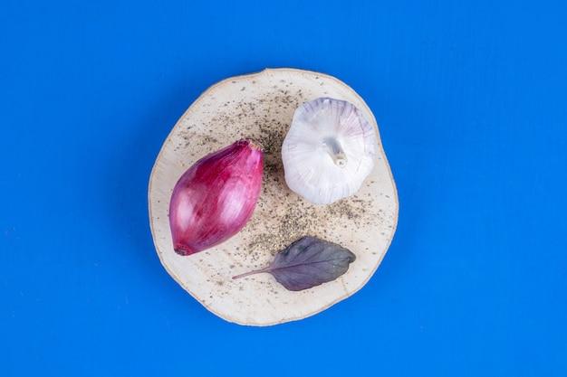 Cebolla morada madura fresca y ajo en pieza de madera.