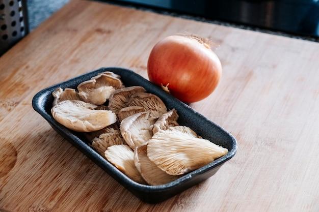 Una cebolla sin pelar y una bandeja con champiñones encima de una tabla de madera