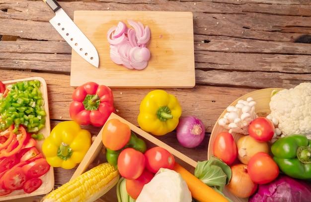Cebolla en rodajas en la tabla de cortar y verduras