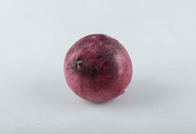 Cebolla roja madura fresca sobre fondo blanco.