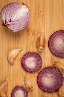 Cebolla roja medio cortada con rollos de cebolla y ajos.