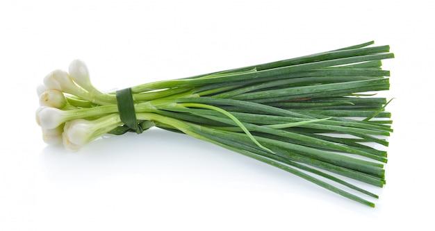 Cebolla verde aislada en la superficie blanca
