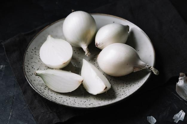 Cebollas blancas en un plato con fondo negro