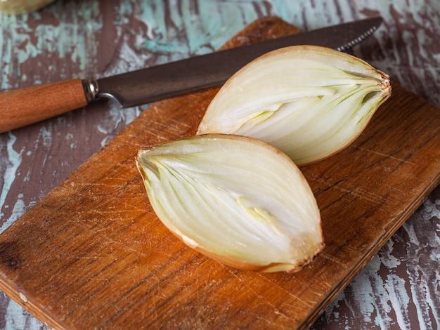 Cebollas cortadas en mitades sobre una tabla de cocina y un cuchillo de cocina de cerca