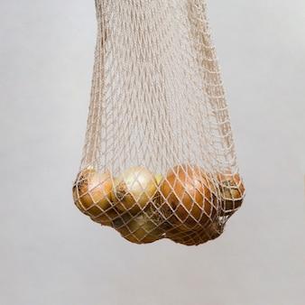 Cebollas frescas en la red blanca colgante contra la pared gris