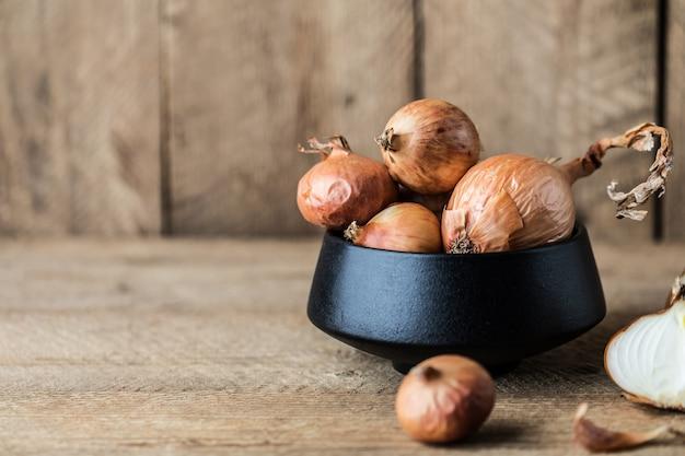 Cebollas frescas sobre fondo de madera rústica.