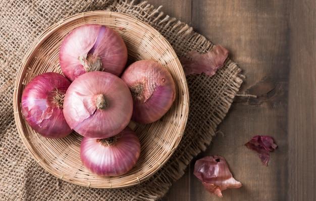 Cebollas rojas en cesta de bambú y en el fondo de madera, vegetales para cocinar los alimentos