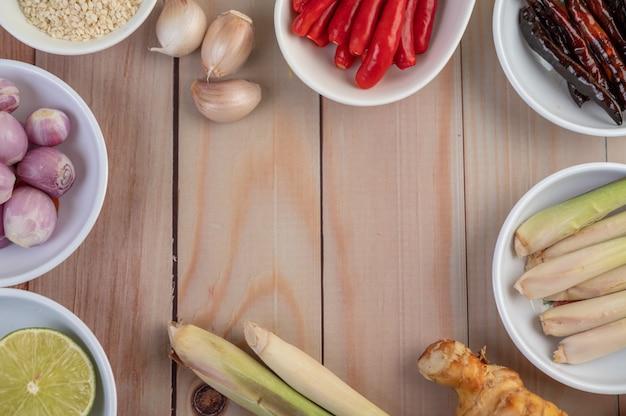 Cebollas rojas, limón, hierba de limón, chiles, ajo, galanga y lechuga en una taza sobre un piso de madera.