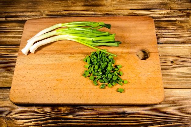 Cebollas verdes picadas en la tabla de cortar sobre la mesa de madera