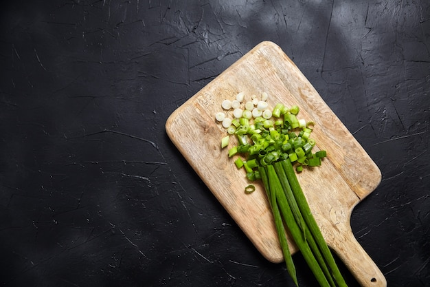 Cebolleta fresca en rodajas sobre una tabla de cortar en el cuadro negro