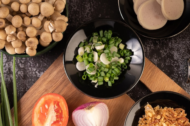 Cebolleta picada en un plato negro con ají, tomate y ajo