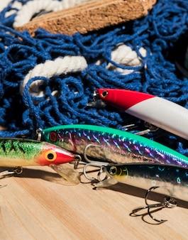 Cebos de pesca coloridos con la red en el escritorio de madera