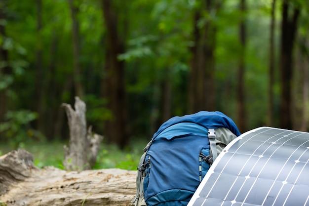 Celda solar con mochila color azul en el bosque.
