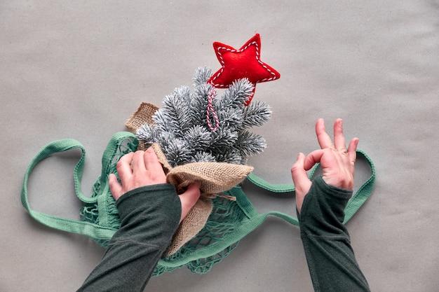 ¡celebra con un árbol falso sin matar a un árbol real! árbol de navidad de plástico con estrella roja en bolsa de cadena, muestra a mano el signo ok.