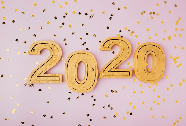 Celebración de año nuevo 2020 y estrellas de brillo dorado