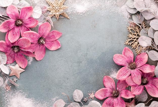 Celebración de año nuevo y fondo de navidad con flores rosas, nieve, estrellas y vista superior de adornos navideños.