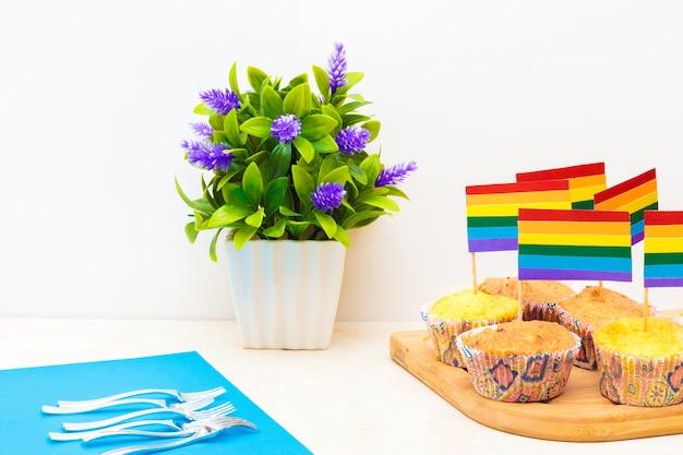 Celebración del día del orgullo con banderas en cupcakes, con una flor en una maceta sobre fondo blanco.