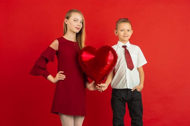 Celebración del día de san valentín, felices, lindos niños caucásicos aislados en estudio rojo