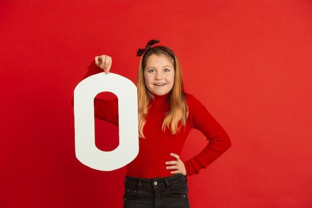Celebración del día de san valentín, feliz niña caucásica sosteniendo una carta sobre fondo rojo.