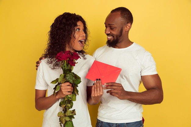 Celebración del día de san valentín, feliz pareja afroamericana aislada sobre fondo amarillo