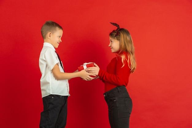 Celebración del día de san valentín, niños caucásicos felices aislados sobre fondo rojo