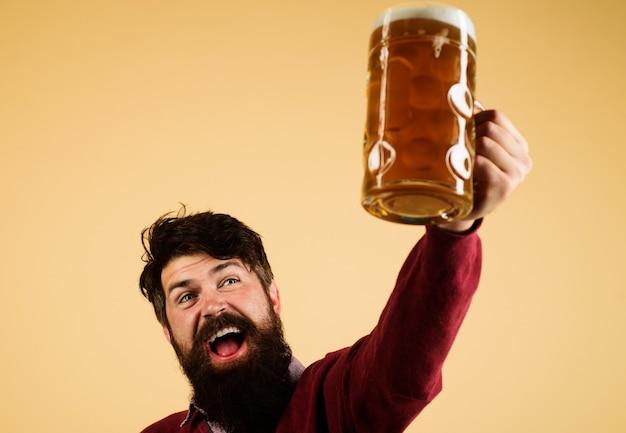 Celebración del festival oktoberfest. hombre barbudo con vaso de tostado de cerveza lager.
