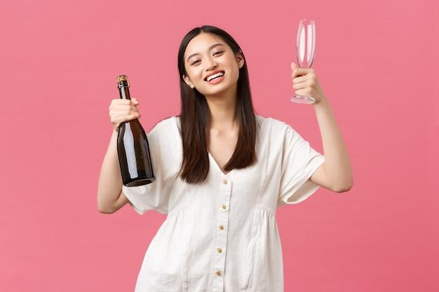 Celebración, fiestas y concepto de diversión. chica asiática feliz alegre lista para disfrutar del día libre con amigas, traer champán y copas, cámara sonriente, fondo rosa alegre de pie.