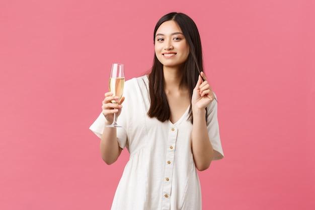 Celebración, fiestas y concepto de diversión. elegante mujer joven y bonita asistir al evento, bebiendo champán y sonriendo con alegría, disfrutando de la celebración, de pie con un vestido blanco sobre fondo rosa.