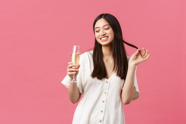 Celebración, fiestas y concepto de diversión. mujer joven coqueta y coqueta con copa de champán tratando de seducir al chico en la celebración del evento, riendo y sonriendo tontamente sobre fondo rosa.