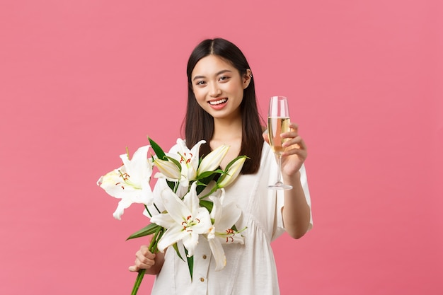 Celebración, fiestas y concepto de diversión. sonriente mujer asiática bastante glamour en vestido con ramo de lirios blancos, levantando una copa de champán para hacer un brindis, bebida para la cumpleañera