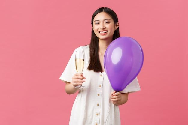 Celebración, fiestas y concepto de diversión. tierna mujer bastante asiática en vestido blanco, sosteniendo un globo y una copa de champán, haciendo tostadas durante el evento, disfrutando del momento, fondo rosa.