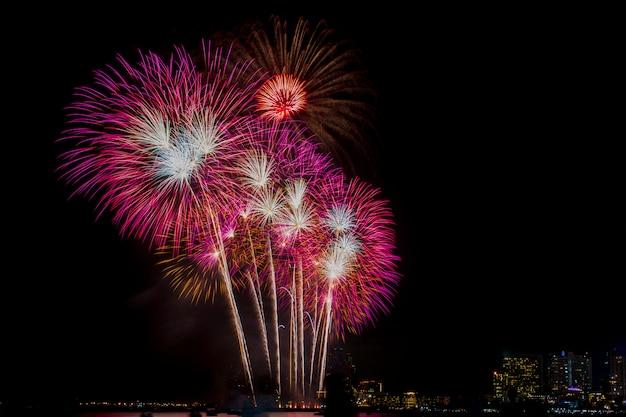 Celebración de los fuegos artificiales en el cielo nocturno, fondo del edificio.