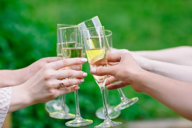 Celebración, gente sosteniendo copas de champán haciendo un brindis