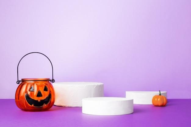 Celebración de halloween. varias calabazas decarativas en podios redondos blancos sobre fondo púrpura