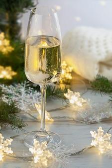 Celebración de navidad y año nuevo con una copa de champán y decoración brillante