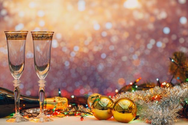 Celebración de nochevieja con champán y un par de copas con decoración navideña. concepto de fiesta y celebración.