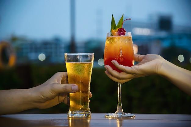 Celebración de pareja en restaurante con refrescos cerveza y mai tai o mai thai