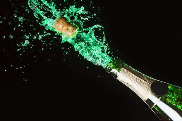 Celebración del tema del alcohol con explosión de salpicaduras de absenta verde