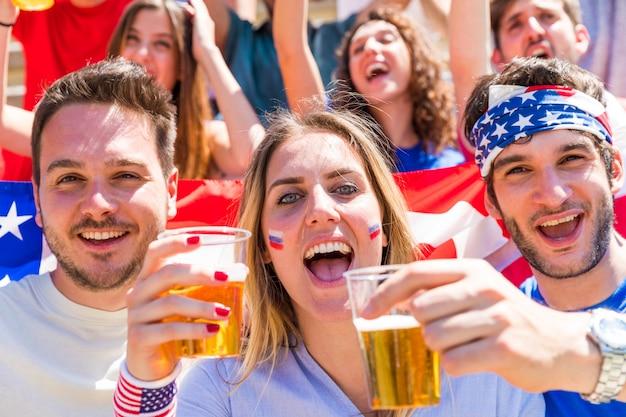 Celebraciones del cuatro de julio, estadounidenses aplaudiendo con cervezas y banderas de los estados unidos.