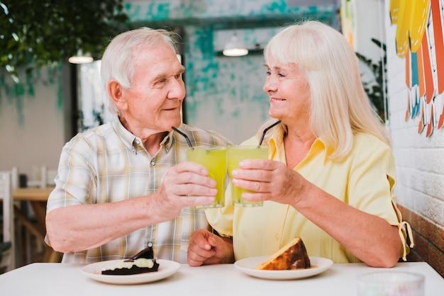 Celebrando alegre pareja de ancianos con bebidas