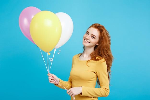 Celebrando el concepto de cerca retrato feliz joven hermosa atractiva pelirroja chica sonriendo con colorido globo de fiesta azul pastel pared