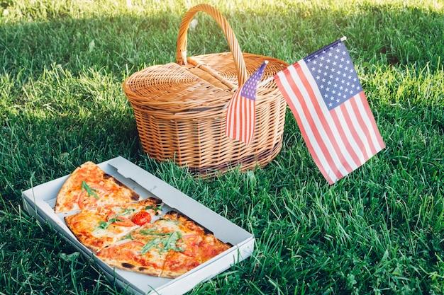 Celebrando el día de la independencia de américa con pizza. cesta de picknick con la bandera de estados unidos.