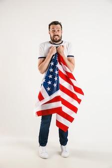 Celebrando un día de la independencia. estrellas y rayas. hombre joven con la bandera de los estados unidos de américa aislado en la pared blanca del estudio. parece loco feliz y orgulloso como un patriota de su país.
