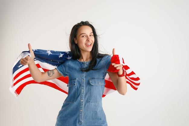 Celebrando un día de la independencia. estrellas y rayas. mujer joven con la bandera de los estados unidos de américa aislado en la pared blanca del estudio. parece loca, feliz y orgullosa como una patriota de su país.