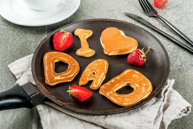 Celebrando el día del padre. desayuno. la idea de un desayuno abundante y delicioso: panqueques en forma de felicitaciones