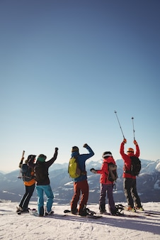 Celebrando a los esquiadores de pie en la montaña cubierta de nieve