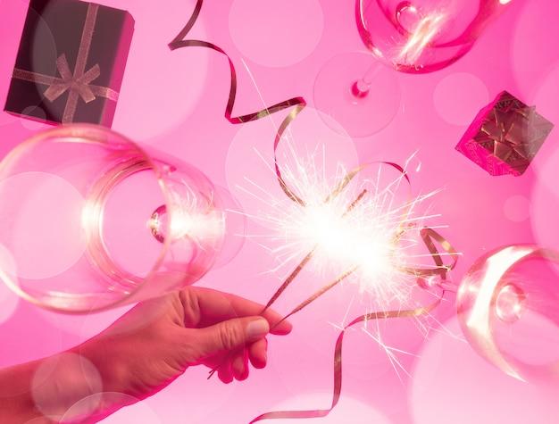 Celebrando la fiesta de navidad o año nuevo con luces de bengala en manos femeninas, cajas de regalo, serpentinas y copas de champán