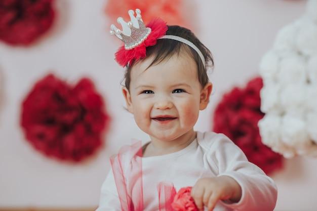 Celebrando el primer cumpleaños. feliz princesita en fiesta de chicas rosa