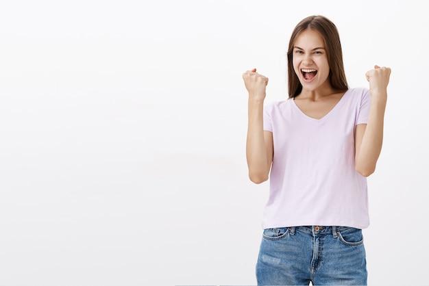 Celebrando y triunfando a una chica guapa feliz levantando los puños cerrados en un gesto de sí regocijándose por lograr un buen resultado sintiéndose alegre por la victoria sobre la pared blanca